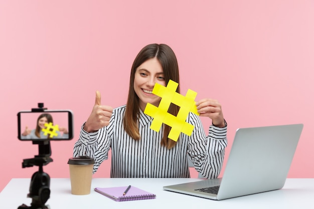 Positive lächelnde bloggerin, die eine videobotschaft auf dem smartphone für ihre anhänger aufzeichnet und das gelbe hashtag-zeichen zeigt, das bittet, beitrag zu bewerten. innenstudioaufnahme lokalisiert auf rosa hintergrund