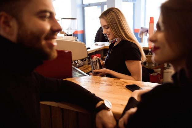 Positive lächelnde frau, die kaffee am zähler zubereitet. modellkonzept für echte menschen