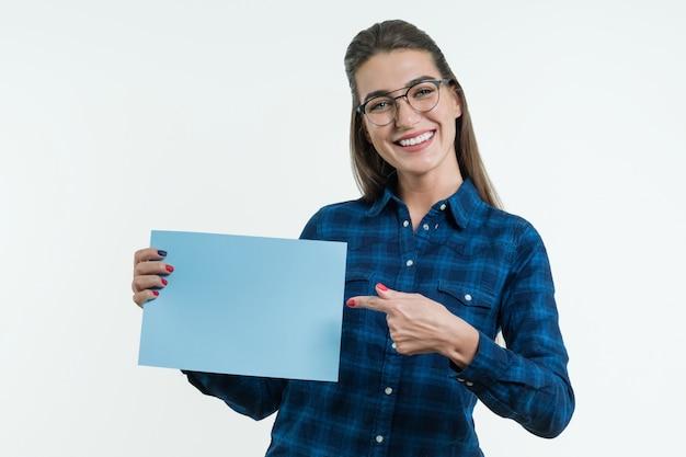 Positive lächelnde studentin, die einen finger auf papier zeigt.