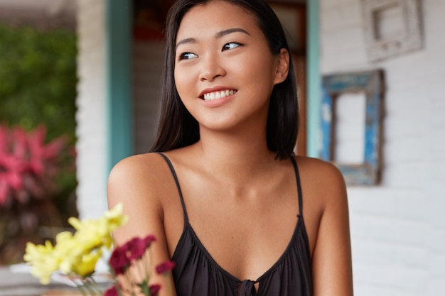 Positive lächelnde zufriedene chinesische frau mit gesunder haut, die lässig auf einem café gekleidet ist