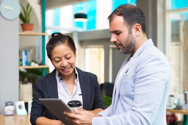 Positive lateinische und asiatische experten, die kaffee und tablette halten