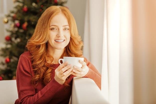Positive lebenseinstellung. lächelnde frau von himmlischer schönheit, die sich auf einem sofa entspannt und ihre tasse warmen tee an einem weihnachtsmorgen genießt.