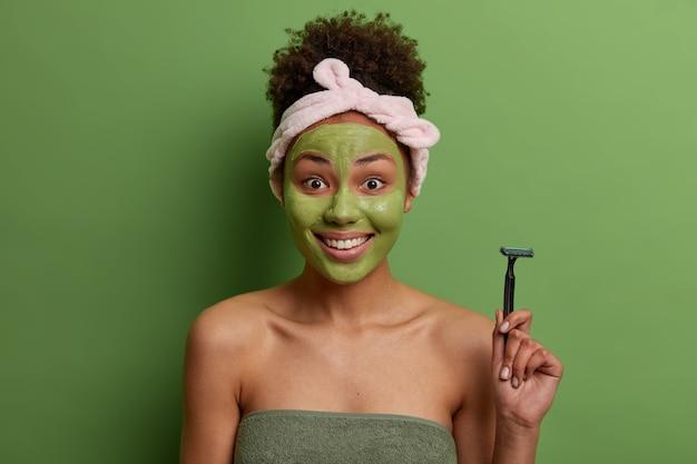 Positive lockige frau hält rasiermesser, geht, um beine zu rasieren, trägt feuchtigkeitsmaske auf gesicht auf, kümmert sich um sich selbst, eingewickelt in badetuch, isoliert über grüner wand. wohlbefinden, reinheit, hygiene