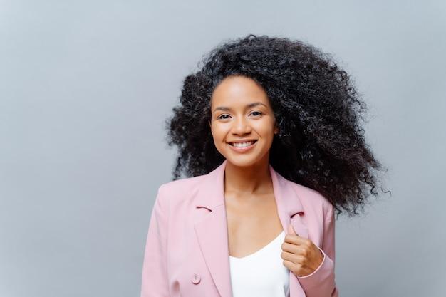 Positive lockige frau mit dem leuchtenden haar und beiläufiger kleidung