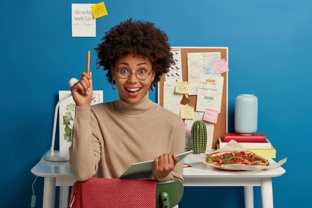 Positive lockige frau schreibt notizen in tagebuch, kreiert lustige geschichte, trägt brille mit guter linse, hebt hand mit stift