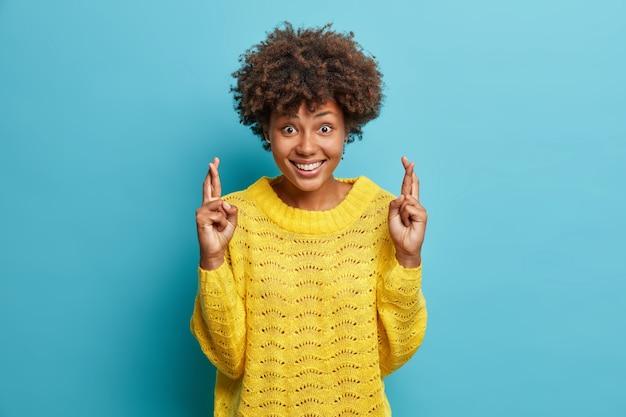 Positive lockige junge frau trägt lässigen gelben pullover kreuzt die finger für viel glück glaubt träume werden wahr lächeln lächelt froh macht wunsch isoliert über blaue wand