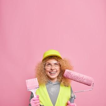 Positive lockige weibliche dekorateurin hält malwerkzeuge, um die wohnung neu zu dekorieren und wände zu streichen, trägt eine schutzhelmbrille und eine uniform, die oben isoliert auf rosa konzentriert ist