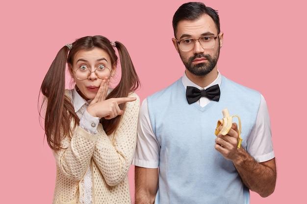 Positive lustige weibliche wonk hat dunkles haar in zwei pferdeschwänzen gekämmt, zeigt auf besten freund, der banane isst, gekleidet in elegante kleidung