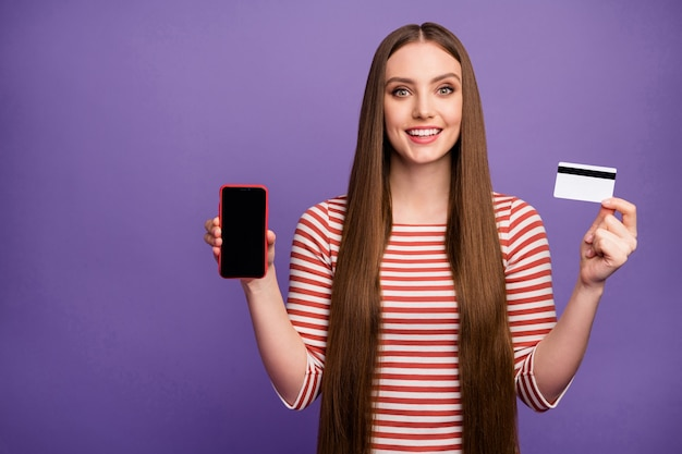 Positive mädchen hipster halten smartphone kreditkarte präsentieren moderne technologie förderung sie zahlen einfache bank zahlungsservice tragen gestreiften weißen pullover pullover isoliert lila farbe wand