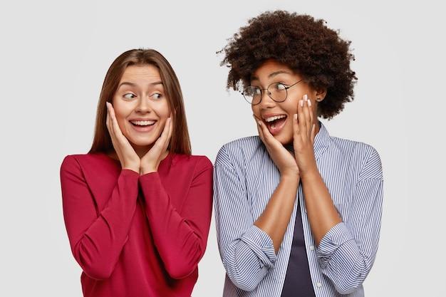 Positive mädchen verschiedener rassen, halten die hände auf den wangen, sind in hochstimmung, freuen sich über das treffen,