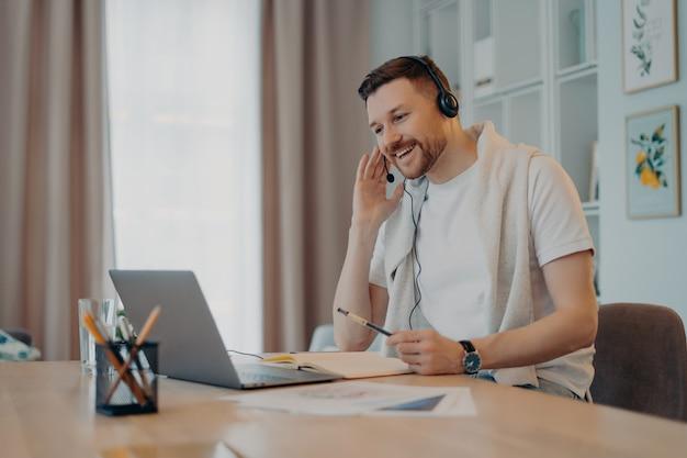 Positive männliche freiberufler oder studenten posieren im home office trägt headset nimmt am bildungs-webinar teil, macht notizen auf dem laptop-display froh, macht videoanrufe lässig gekleidet. web-kommunikation