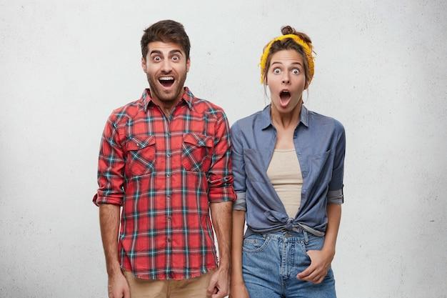 Positive menschliche emotionen, gefühle, einstellungen und reaktionskonzepte. porträt des überraschten jungen bärtigen mannes im roten karierten hemd und in der frau mit dem stirnband, das aufwirft