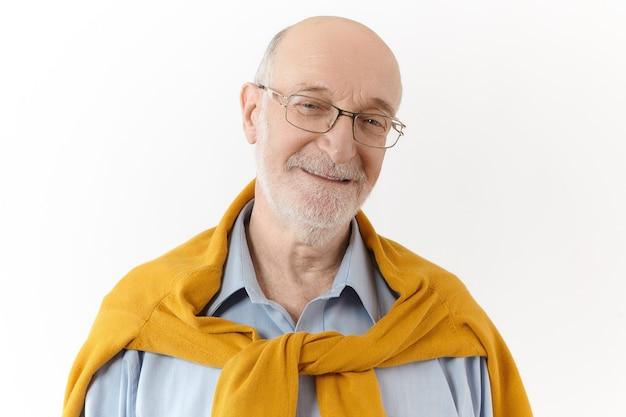 Positive menschliche emotionen, gefühle und einstellungen. bild des glücklichen attraktiven pensionierten mannes mit weißem bart und kahlem kopf, der freude und vergnügen ausdrückt und kamera mit fröhlichem freundlichem lächeln betrachtet