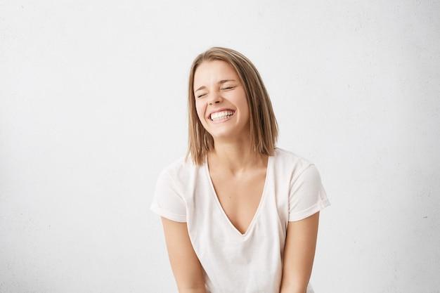 Positive menschliche gefühle. kopfschuss eines glücklichen emotionalen teenager-mädchens mit bob-haarschnitt, das aus tiefstem herzen lacht, die augen geschlossen hält und perfekte weiße zähne zeigt, während es drinnen spaß hat