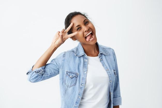 Positive menschliche gefühle. porträt der entspannten sorglosen afroamerikanischen frau mit dem lächeln, das ihre zunge und v-zeichen zeigt, die jeanshemd tragen, das ein auge fest schließt, während sie spaß mit freunden drinnen hat