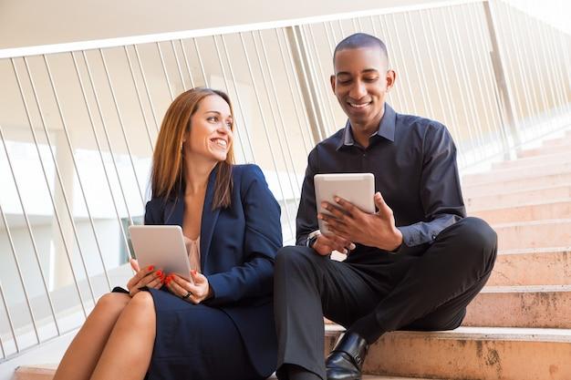 Positive mitarbeiter, die tabletten halten und auf treppe sitzen