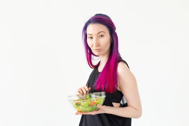 Positive mixed race hipster mädchen mit farbigen haaren, die nach dem körperlichen training auf weißem hintergrund einen hellen griechischen salat essen. das konzept der richtigen ernährung und gewichtsabnahme. platz für werbung