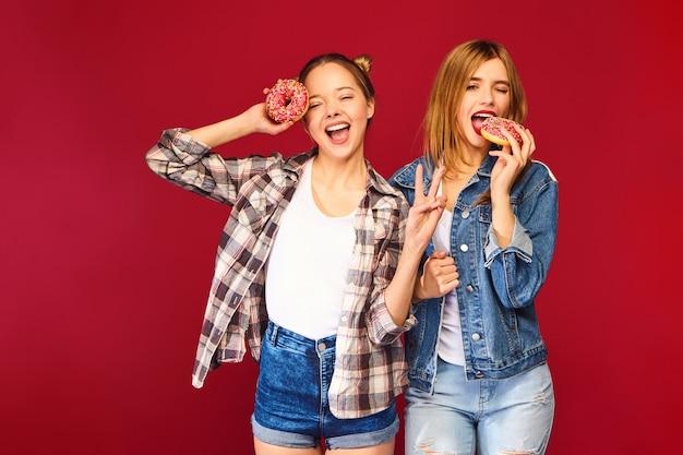 Positive modelle halten frische rosa donuts mit pulver bereit, um süßigkeiten zu genießen