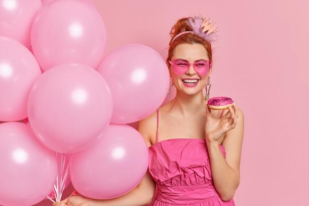 Positive modische rothaarige frau lächelt breit hat festliche stimmung hält leckere donut aufgeblasene ballons trägt herzförmige sonnenbrille und kleid