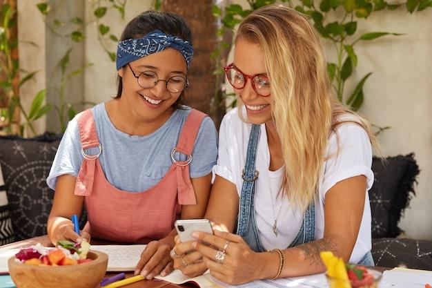 Positive multiethnische studenten mit fröhlichem ausdruck sehen sich videos aus sozialen netzwerken an und sehen sich fotos an