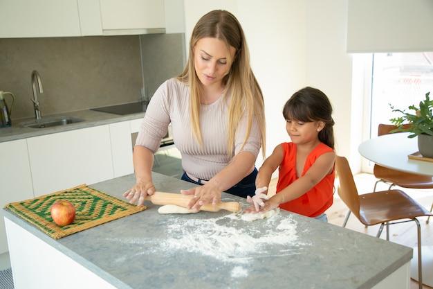 Positive mutter und tochter, die teig auf küchentisch rollen. mädchen und ihre mutter backen zusammen brot oder kuchen. mittlerer schuss. familienkochkonzept
