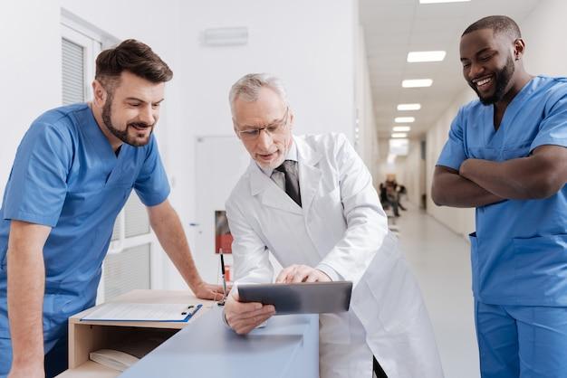 Positive nachrichten teilen. herrlicher, freundlicher, erfahrener praktiker, der im krankenhaus arbeitet und geräte verwendet, während er sich mit kollegen unterhält