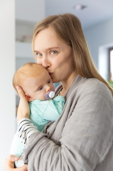 Positive neue mutter, die baby küsst und streichelt
