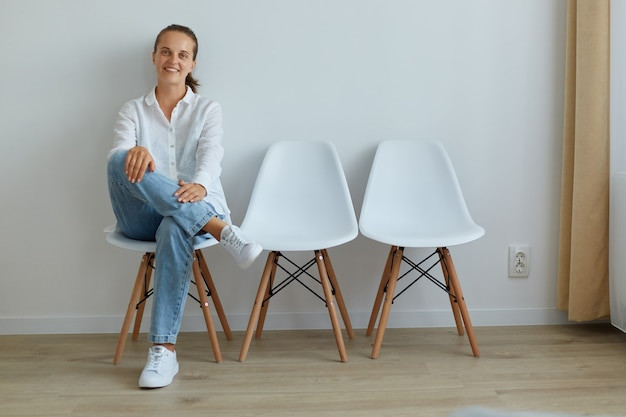 Positive optimistische frau mit freundlichem lächeln, die auf einem stuhl gegen eine helle wand im innenbereich sitzt, die kamera mit glücklichem und selbstbewusstem ausdruck betrachtet, weißes hemd und jeans trägt.