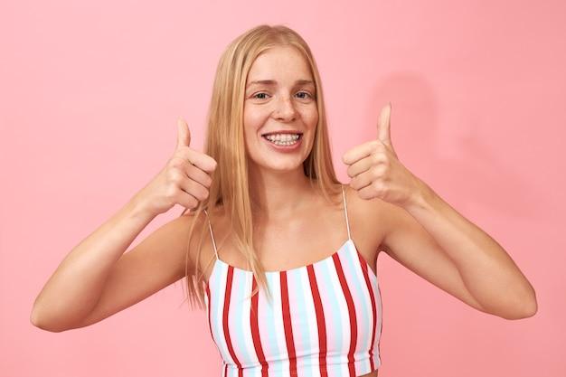 Positive optimistische teenager-mädchen machen daumen geste, ermutigen sie, auf like-button zu klicken, und freuen sich über gute nachrichten