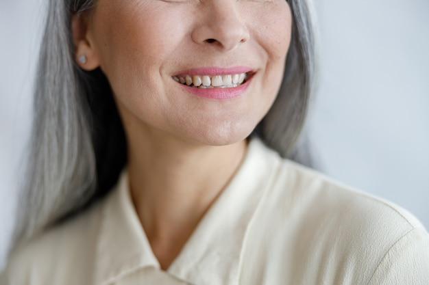 Positive reife dame in beigem hemd lächelt in die kamera und zeigt gesunde zähne auf hellem hintergrund in studio-nahaufnahme