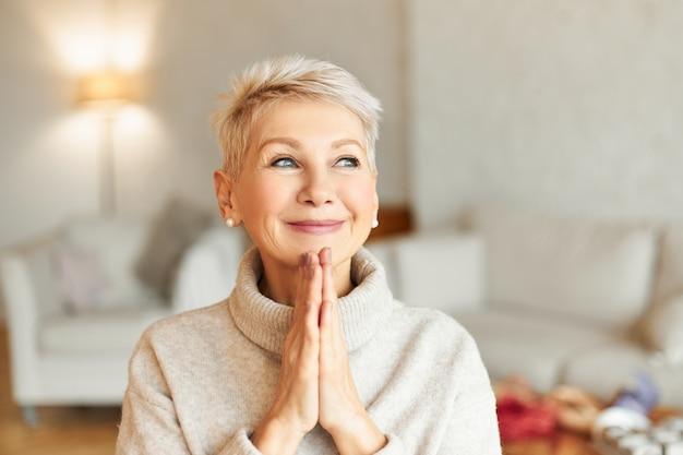 Positive reife europäische frau in warmem pullover mit verträumtem, erstauntem gesichtsausdruck, der die hände zusammenpresst und lächelt, auf das beste hofft und gott um gesundheit und wohlbefinden bittet. glaubenskonzept