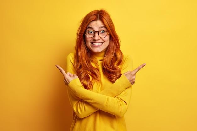 Positive rothaarige europäerin drückt die daumen und zeigt auf verschiedene seiten. zwei varianten zögern zwischen produkten, die in lässigen gelben rollkragenpullis im innenbereich gekleidet sind. was gibt es schöneres zu wählen