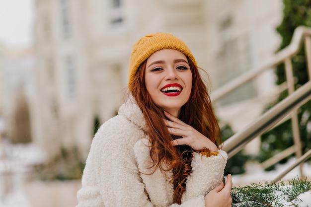 Positive rothaarige frau, die über verschwommene natur lacht. raffiniertes ingwermädchen, das während des winterfotoshootings lächelt.