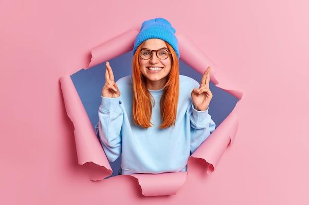 Positive rothaarige kaukasische frau mit zahnigem lächeln kreuzt finger glaubt an glück betet für den erfolg trägt lässigen pullover und hut bricht durch papier