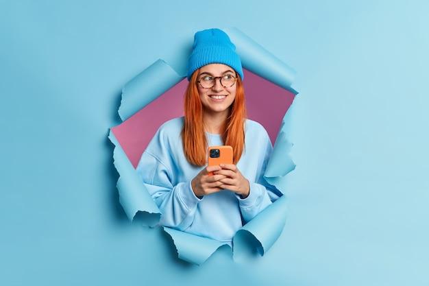 Positive rothaarige teenager-mädchen-technologie benutzer hält handy sendet textnachrichten blicke beiseite trägt gerne blauen hut und pullover sieht nachdenklich beiseite bricht durch blaues papierloch
