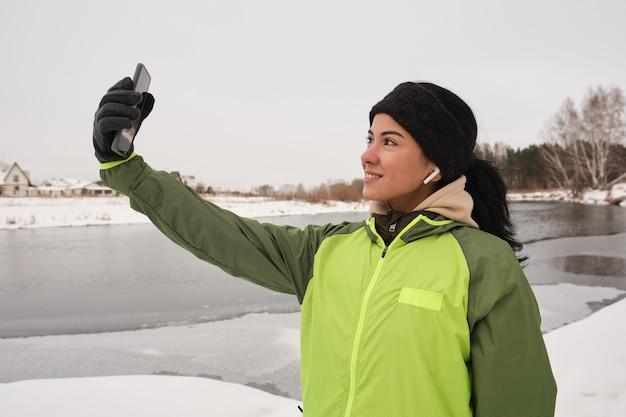 Positive schöne frau in den ohrstöpseln, die auf winterufer stehen und sich auf smartphone-kamera fotografieren