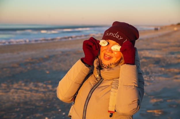 Positive schöne frau mit muscheln hat spaß an der küste an einem sonnigen wintertag.
