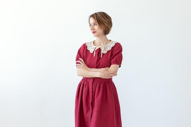 Positive schöne junge lächelnde frau, die auf rotem bescheidenem kleid der weißen wand aufwirft. konzept eines stilvollen jungen mädchens.