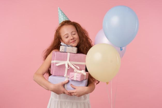 Positive schöne rothaarige weibliche kind mit langen lockigen haaren feiert urlaub, drückt wahre positive emotionen aus, während auf rosa stehen. kinder- und feierkonzept