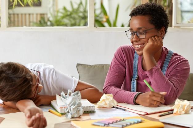 Positive schwarze junge frau schaut auf gruppenmitglied, das sich müde fühlt, bereitet sich gemeinsam auf die bevorstehende prüfung vor, macht sich notizen über kreative ideen, umgeben von papier. teamworking und lernkonzept
