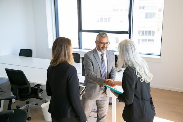 Positive, selbstbewusste geschäftspartner beenden das treffen mit handschlag, im büro und diskutieren die zusammenarbeit. hoher winkel. kommunikations- oder partnerschaftskonzept