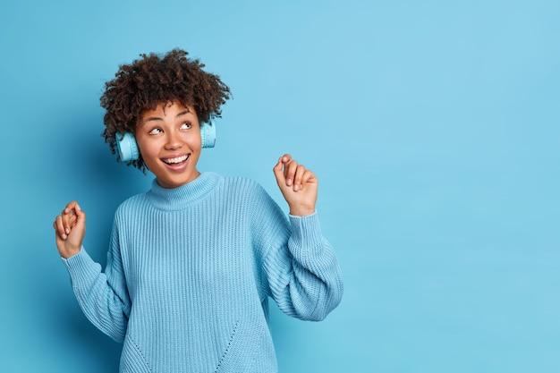 Positive sorglose afroamerikanerin tanzt sorglos hält die arme hoch und lächelt breit hat spaß spaß genießt lieblingsmusik trägt drahtlose kopfhörer in pullover gekleidet