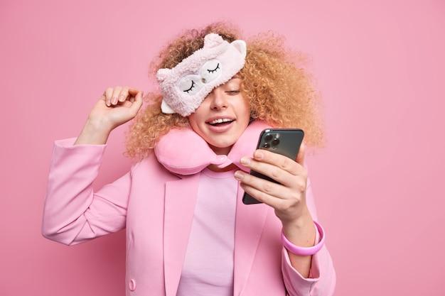 Positive sorglose frau, die süchtig nach modernen technologien ist, überprüft den newsfeed in sozialen netzwerken per smartphone, nachdem sie aufgewacht ist, trägt eine weiche schlafmaske, formelle kleidung, chattet online isoliert auf rosa wand