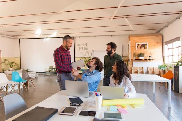 Positive startgruppe mit den laptops, die im konferenzzimmer plaudern