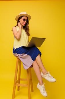 Positive stilvolle frau im hut und im sommerkleid, die mit laptop auf gelber wand arbeiten