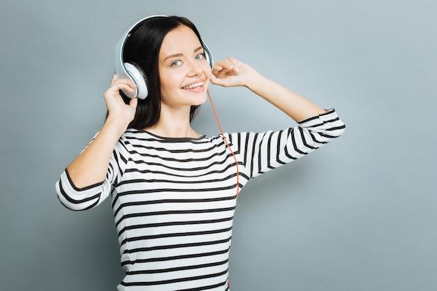 Positive stimmung. attraktive frau, die hände auf kopfhörer setzt und lächeln auf gesicht hält, während sie nach vorne schaut