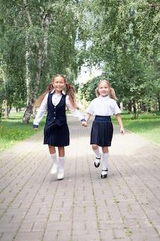 Positive stimmung. mädchen im teenageralter mit rucksäcken im park spazieren. zurück zur schule. jugendlich kinder mit rucksack. konzept der freundschaft. besten schulfreunde. mit spaß zur schule gehen. schulmädchen mit rucksack