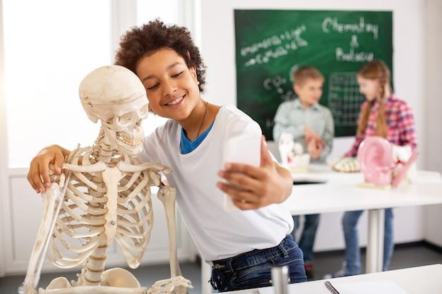 Positive stimmung. netter fröhlicher junge, der ein skelett umarmt, während er selfies mitnimmt