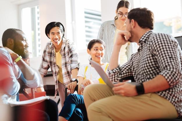 Positive studenten. fröhliche emotionale schüler, die eine gute zeit im unterricht haben und gleichzeitig ein positives brainstorming haben
