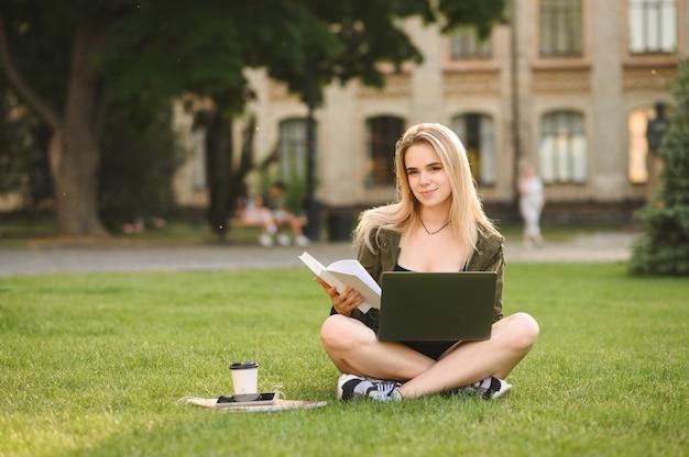 Positive studentin, die mit gekreuzten beinen auf gras sitzt
